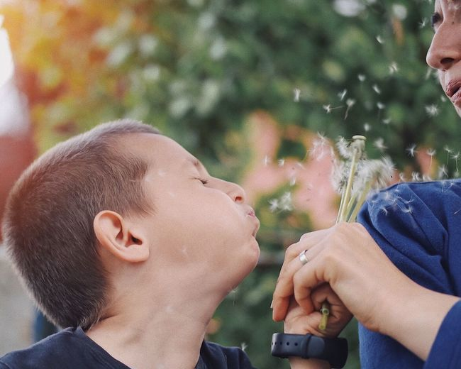 Fun with mom...Kid blowing a dandelion towards his mom... Mother And Son Experience Dandelion Seeds Fluff Dandelion Seeds Education Healthy Lifestyle Happiness Family Fun Vacation Blowing Blowing Dandelion Poof Dandelion Seeds Dandelion Real People Two People Togetherness Men Bonding Lifestyles Leisure Activity Child Childhood Emotion Positive Emotion Family Headshot Focus On Foreground Love