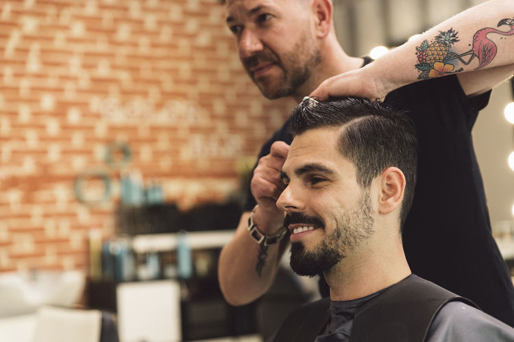 Midsection of barber cutting man hair in salon