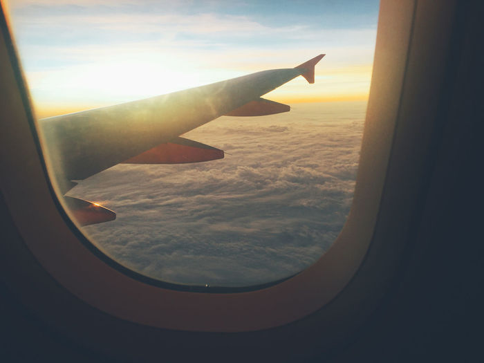 Airplane flying over clouds seen through window