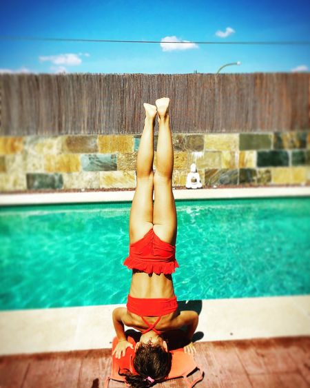 Girl doing headstand at poolside