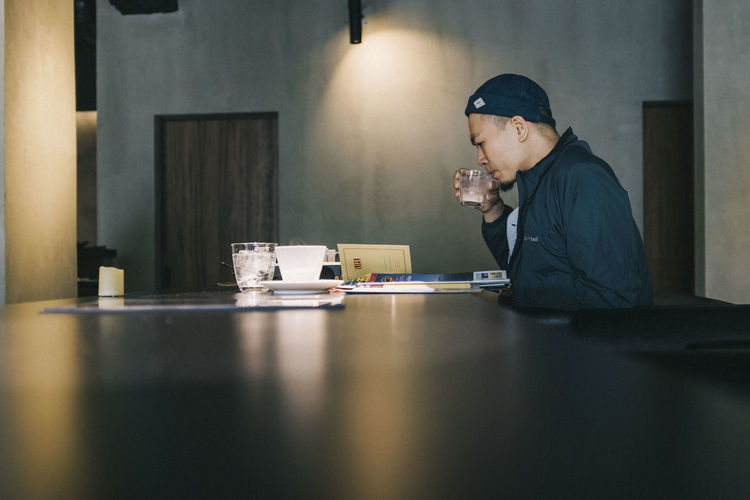 Side view of man drinking coffee at table in cafe