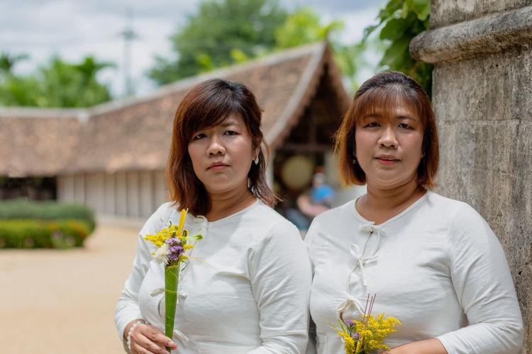 Portrait of women holding flowers