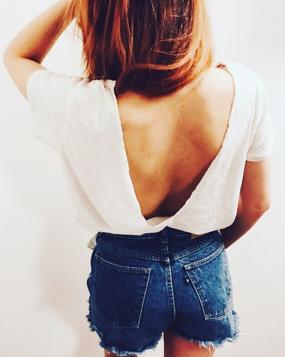 Rear view of young woman backless top against white wall