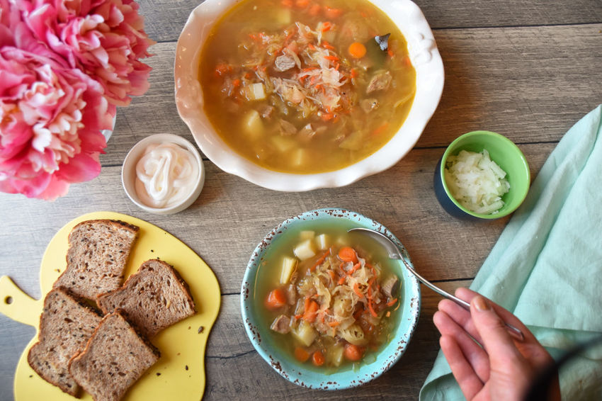 Sauerkraut soup with bread, chopped onions, sour cream Dinner Lunch Side Dish Aqua Bowl Close-up Day Directly Above Eating Soup Flower Food Food And Drink Fresh Freshness Hand Healthy Eating High Angle View Indoors  No People Plate Ready-to-eat Sauerkraut Sauerkraut Soup Sour Cream Table