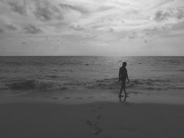 Rear view of man standing on beach against sky