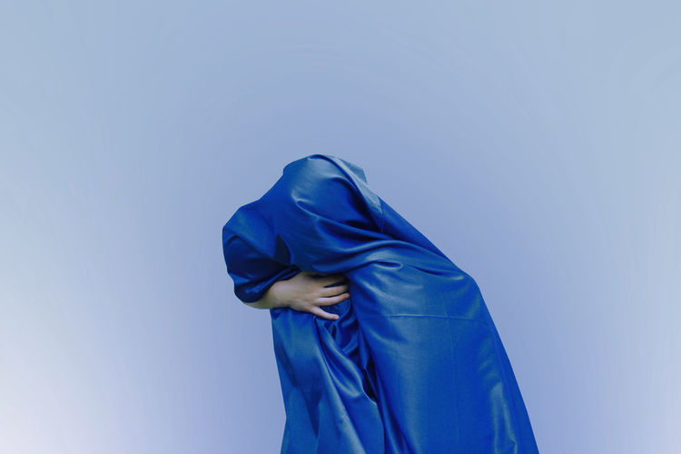 Girl covered with blue fabric against colored background