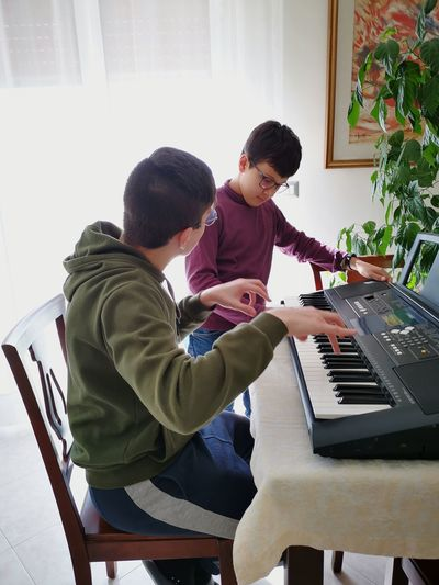 Side view of brothers practicing piano at home