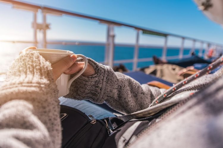 Midsection of woman having drink while sitting in boat