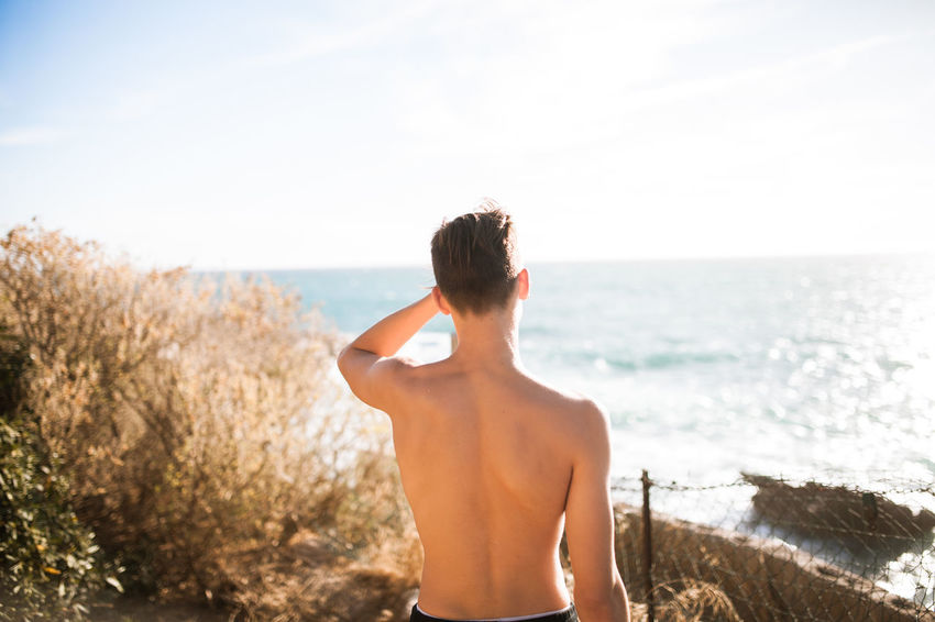 Summertime, and the living is easy. Summer Exploratorium Beach Beauty In Nature Day Hairstyle Horizon Over Water Land Leisure Activity Lifestyles Looking At View Nature One Person Outdoors Real People Rear View Scenics - Nature Sea Shirtless Sky Standing Sunlight Waist Up Water