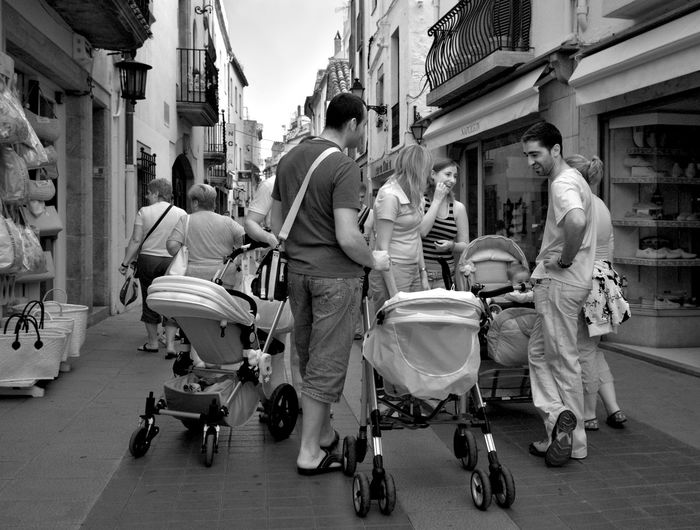 Men and women with baby carriage on street amidst buildings