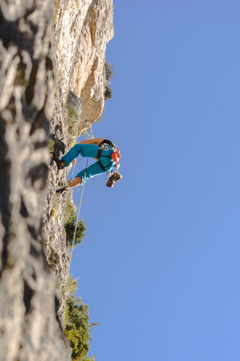 An athlete is climbing, high in the rocks throught the sky and the nature in the Jonte Canyon in the region of Lozère in the South of France. Adults Only Adventure Blue Climbing Climbing Rope Day Extreme Sports Full Length Headwear Helmet Leisure Activity Low Angle View One Person Outdoors RISK Rock - Object Rock Climbing Rope Skill  Sport Sports Helmet Young Adult Go Higher Adventures In The City