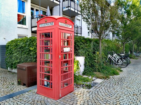 I read about these book exchange phone booths but this is the first one I see in the flesh Telephone Booth Red Pay Phone Communication Telephone Text Built Structure Architecture Building Exterior Day Outdoors No People Convenience Tree City Book Exchange Mini Library