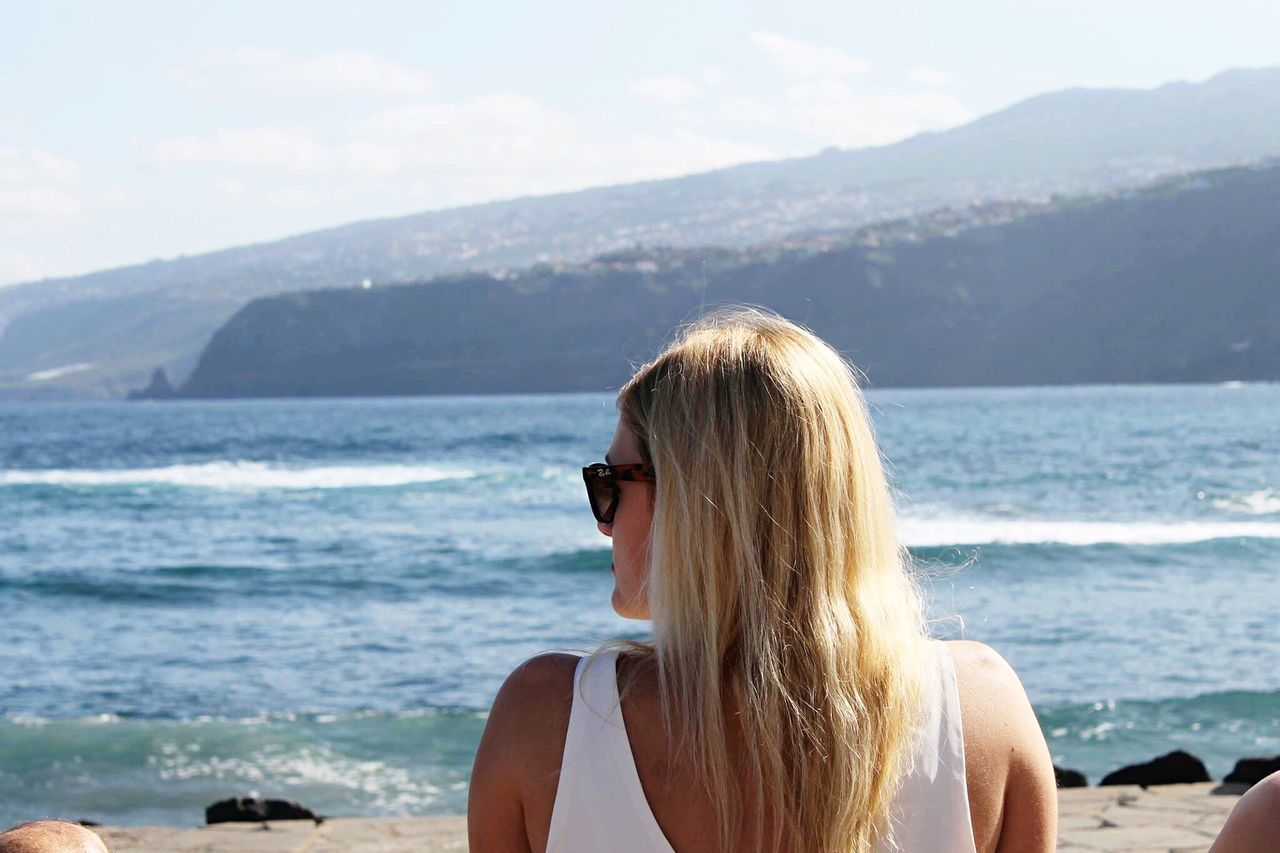 sea, blond hair, one person, young adult, beach, nature, real people, scenics, young women, long hair, day, outdoors, sky, rear view, water, beauty in nature, leisure activity, standing, mountain, lifestyles, tranquility, vacations, horizon over water, beautiful woman, close-up, adult, people