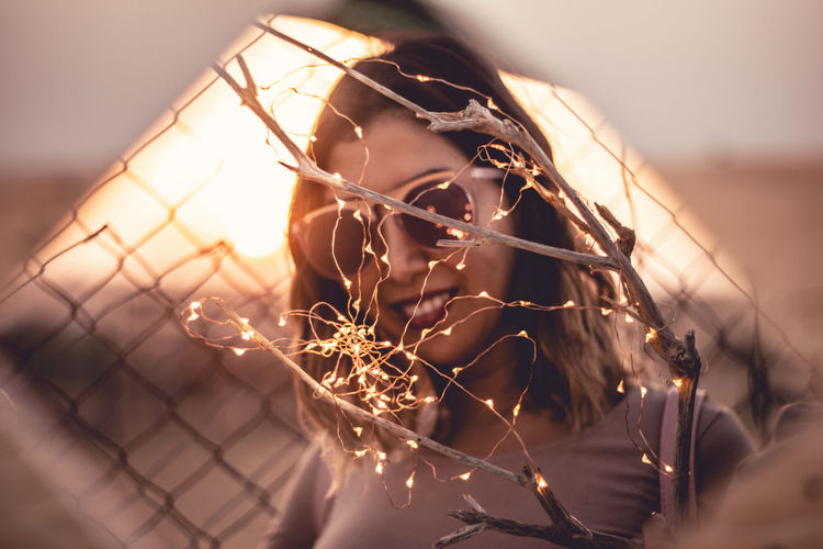 Portrait Of Woman In Sunglasses By Illuminated Lights