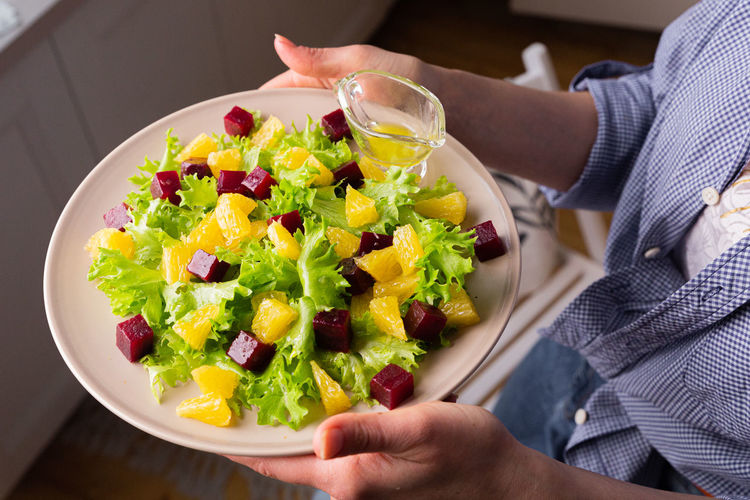 Midsection of person holding vegetables in bowl on table