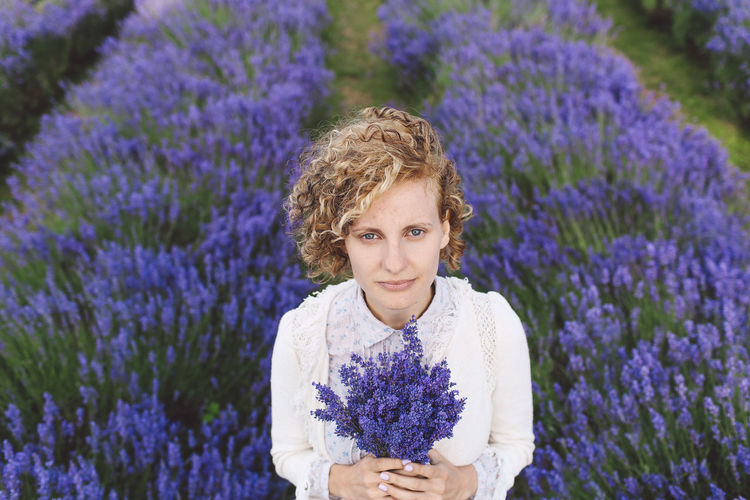 Portrait Of Woman Holding Lavenders While Standing On Field