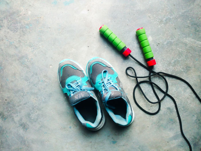 High angle view of shoes with jumping rope on floor