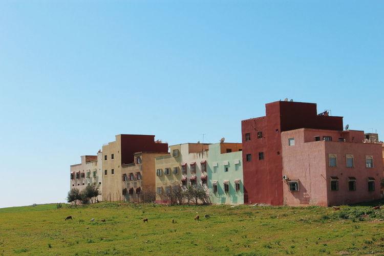 Buildings on field against clear blue sky