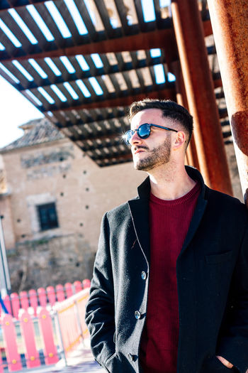 Handsome man wearing sunglasses standing by column