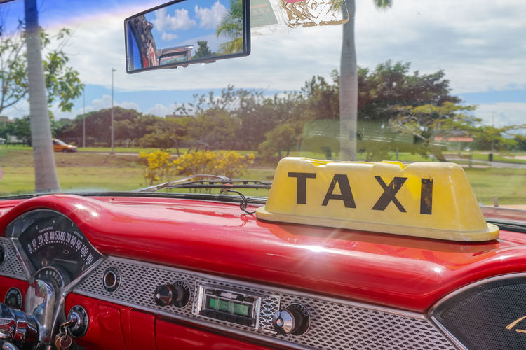 Dashboard of vintage taxi, Cuba, Varadero Mode Of Transportation Day Car Transportation Land Vehicle Outdoors Text Motor Vehicle Red No People Vintage Car Taxi Belair Radio Chrome Windshield Tree Yellow Sign Cuba Varadero Cuba. Varadero