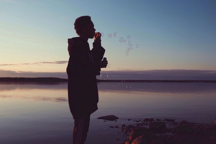 Young man blowing bubbles at sunset