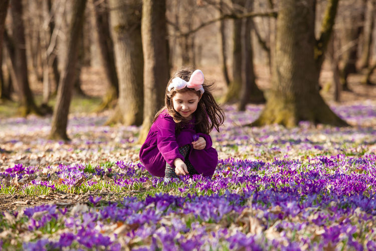 Girl with purple flowers on tree trunk