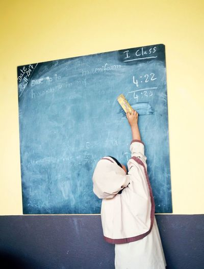 Rear View Of Girl Erasing Blackboard With Duster While Standing In Classroom