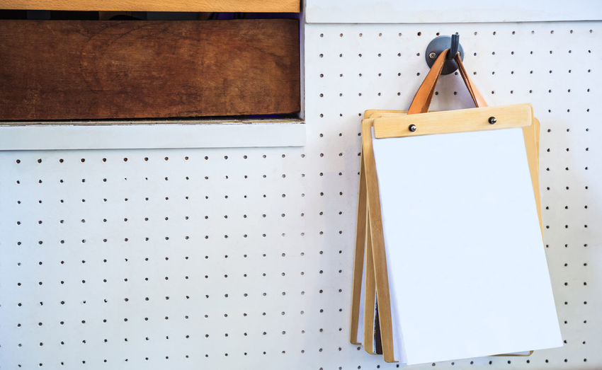Close-up of notepad hanging on pegboard