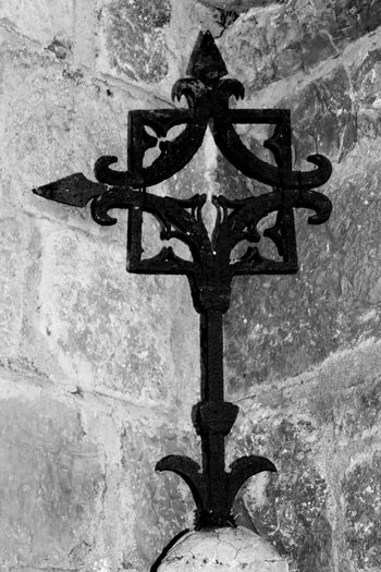 Close-up of cross on cemetery against wall