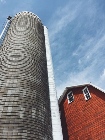 Low angle view of silo and barn against sky