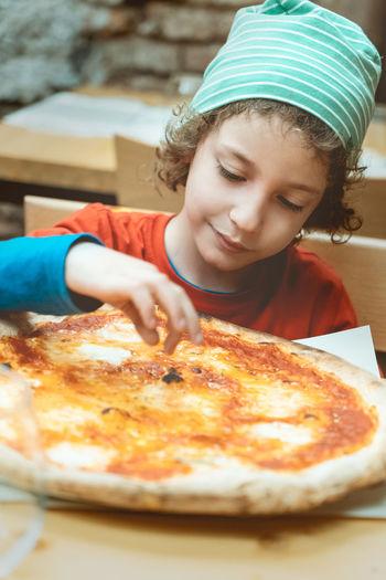 Cute boy having pizza at restaurant