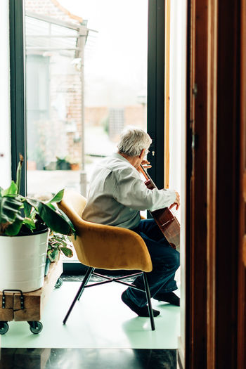 Man sitting on chair by window at home