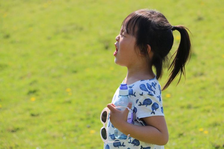 Girl looking away while standing on grassy field
