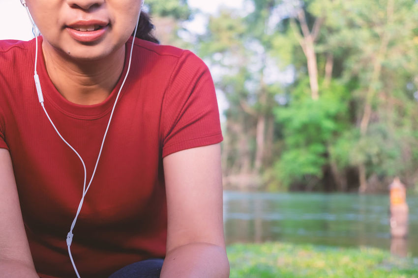 Listening Music Headphones One Person Front View Lifestyles Technology In-ear Headphones Leisure Activity Adult Day Focus On Foreground Sport Mp3 Player Sitting Smiling Casual Clothing Sports Clothing Ear Pieces Vacations Nature River Backgrounds Outdoors Red