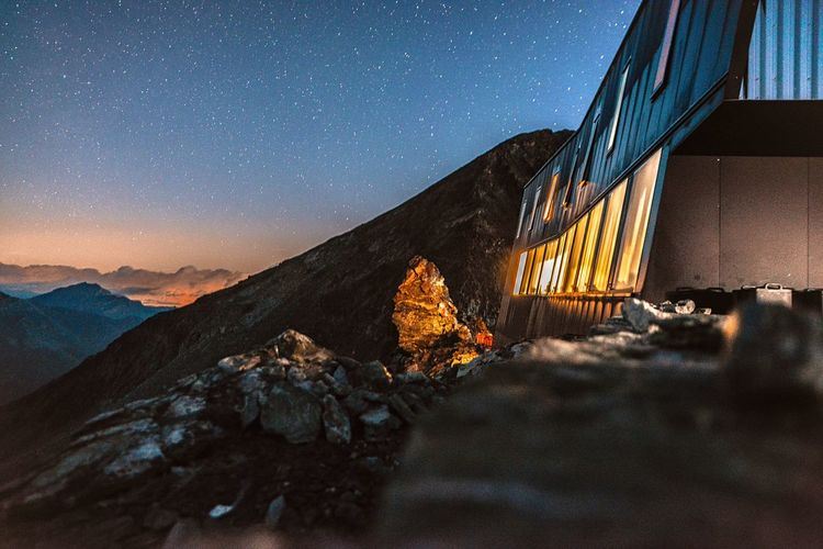 Illuminated House On Rocky Mountain Against Star Field Sky