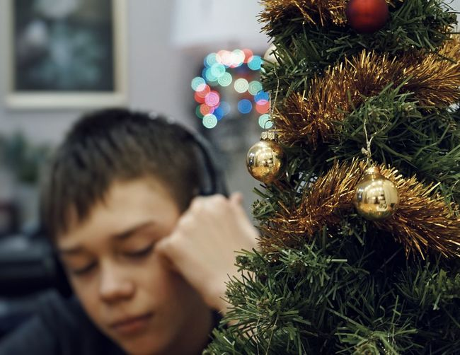 Boy by decorated christmas tree