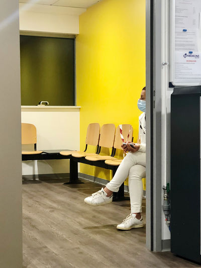 Woman sitting on chair at entrance of building