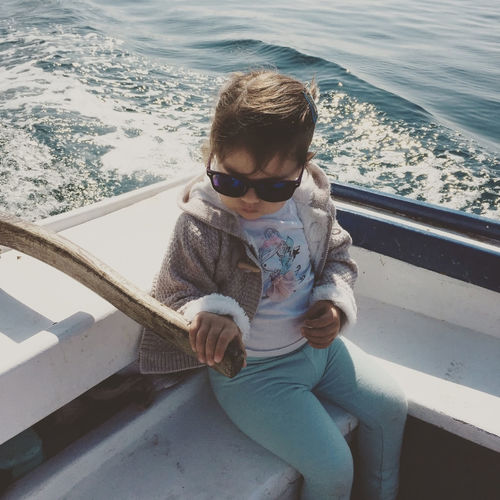 Cute little girl sailing with classic wooden boat Boat Casual Clothing Caucasian Child Childhood Day Girl Kid Leisure Activity Lifestyles Little Marine Nautical Vessel Outdoors Railing Sail Sailing Sailor Sea Sitting Small Toddler  Transportation Vessel Water
