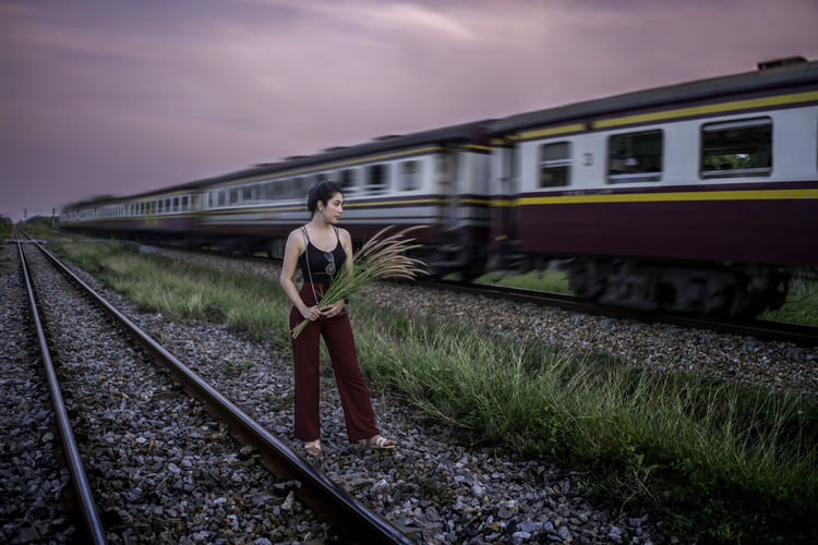 Woman holding plant while standing against train