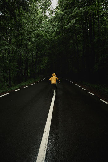 Rear view of child walking on road amidst trees