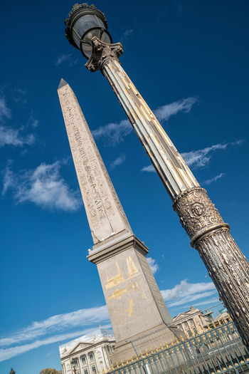 Low angle view of obelisk against blue sky in city
