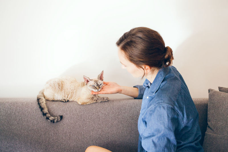 Side view of woman sitting with cat on sofa at home