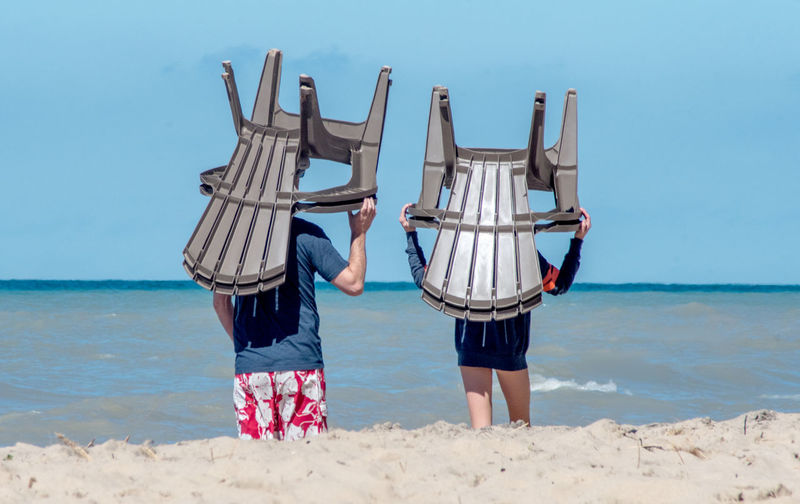 A couple carry plastic beach chairs on their head ,moving them closer to the water