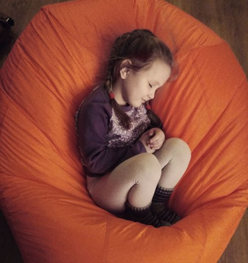High Angle View Of Girl Sleeping On Orange Bean Bag At Home