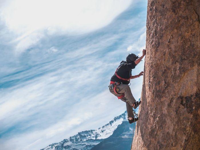 Man climbing cliff against sky