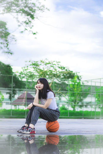 Full length of young woman sitting at basketball court