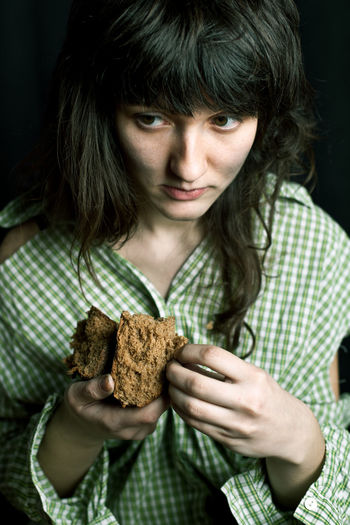 Homeless woman looking away while holding bread