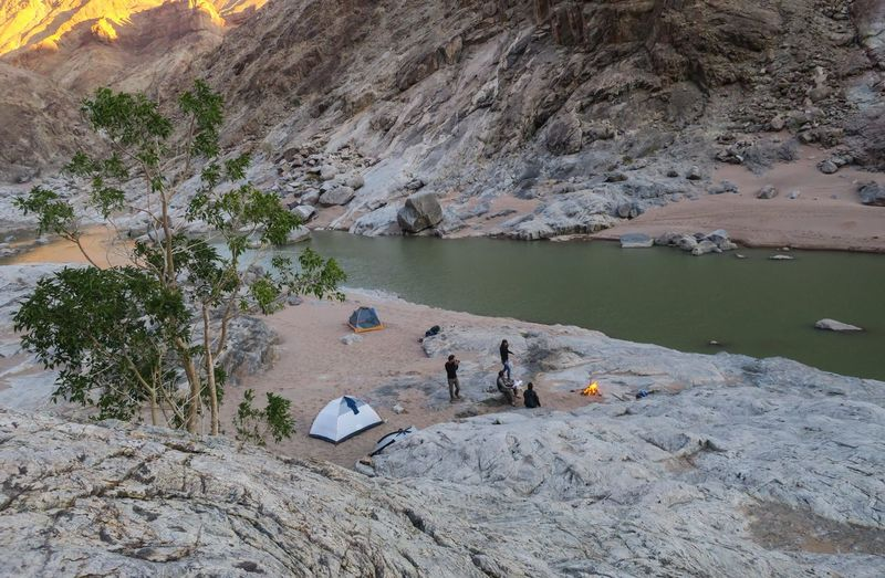 Group of hikers camping alongside a river in scenic canyon Adventure Arid Climate Barbecue Campfire Camping Evening Friends Group Group Of People Lake Let's Go. Together. Mountain Namibia Nature Outdoor Photography Outdoors People River Rock - Object Sand Tent Travel Tree Water Wilderness