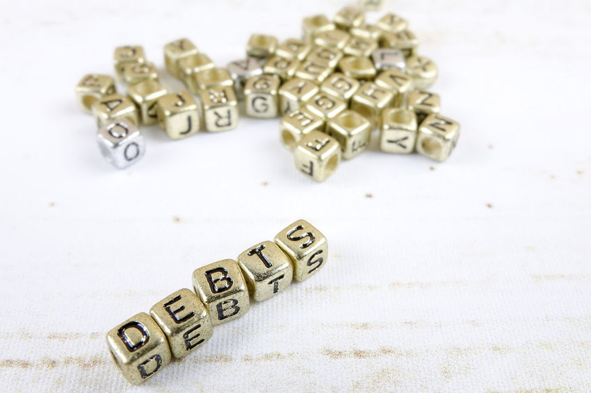 DEBT CONCEPT WITH GOLD DICE ON A WOODEN TABLE Close-up Communication Credit Card Debt Crisis Focus On Foreground High Angle View Indoors  Large Group Of Objects Man Made Man Made Object Metal No People Number Still Life Studio Shot Table Text Toy Wealth Western Script White Background
