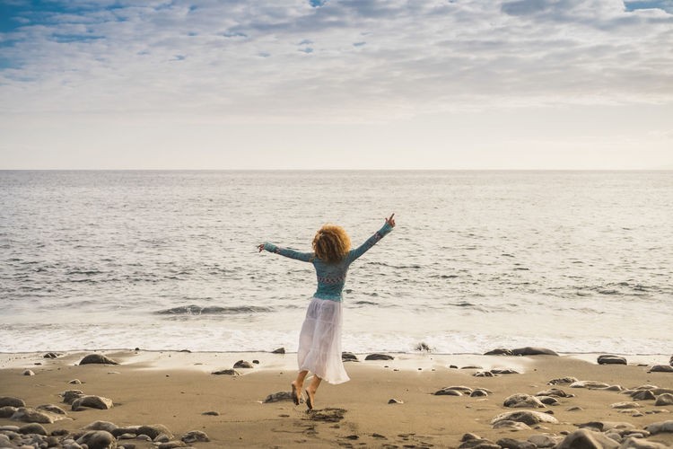 Rear view of woman dancing at beach against cloudy sky